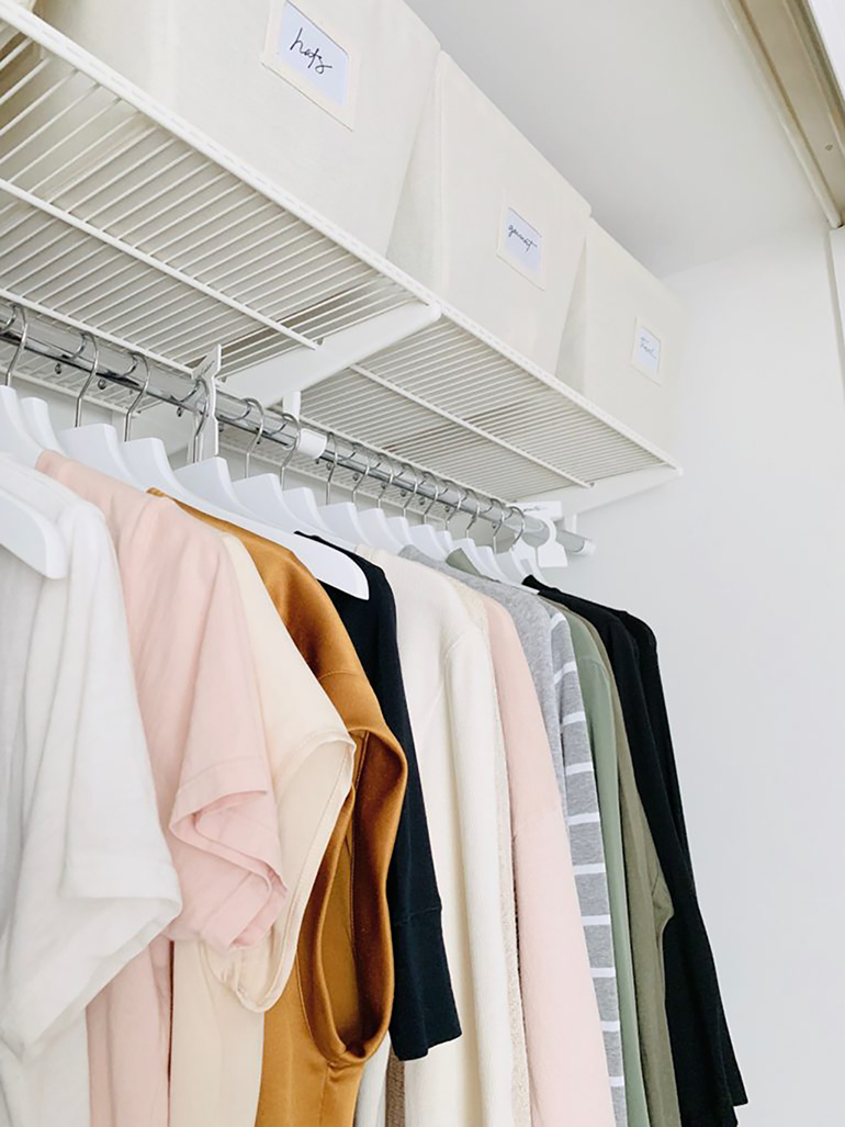Organized closet with color coded clothes.