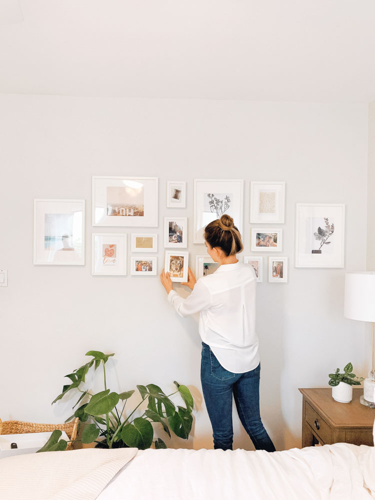 Nicole hangs framed photos in her gallery wall.